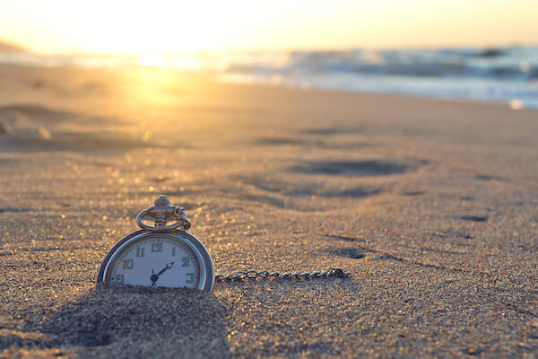 clock sinking in white sand at sunset on a beach